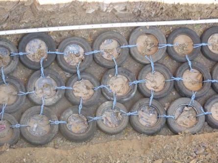 Нижний ряд подпорной стенки из шин. Крепление шин пропиленовыми канатиками.